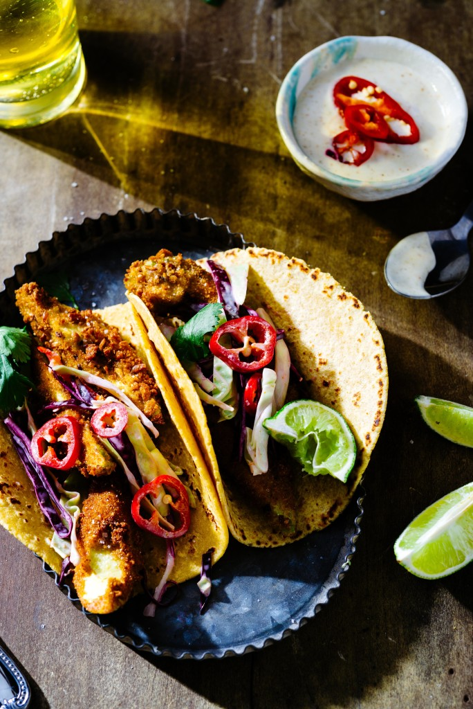 Overhead of fried avocado tacos with red cabbage slaw and sliced red jalapenos in metal tray with lime wedges, creamy sauce and beer on wooden surface.