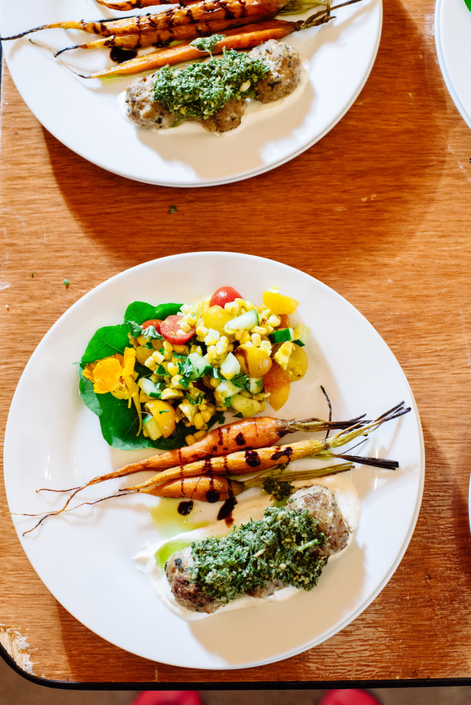 Overhead of white plate with roasted carrots and balsamic drizzle with lamb meatballs and greens pesto and corn salad.