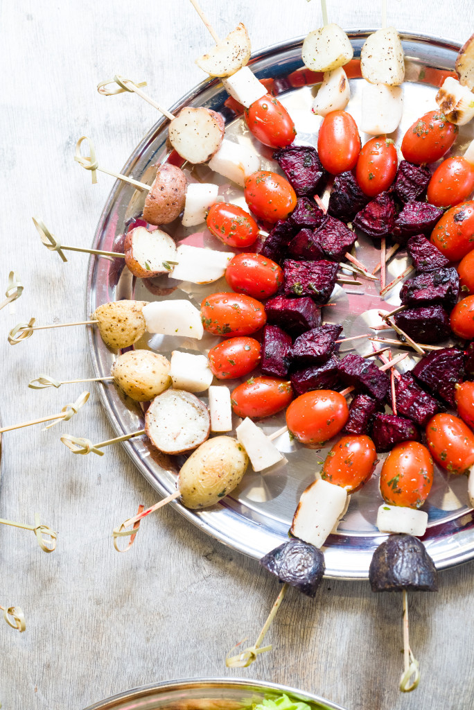 Colorful vegetable skewers or kabobs on a silver tray at a party.